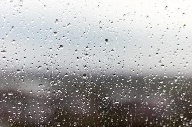 Close-up shot van een raam op een regenachtige dag, regendruppels die door het raam rollen