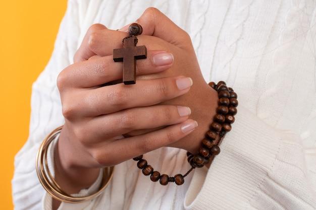 Close-up shot van een rozenkrans met een kruis in de handen van de vrouw