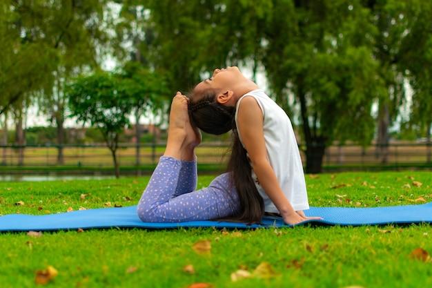 Close-up shot van een schattig latijns meisje dat yoga beoefent in een park