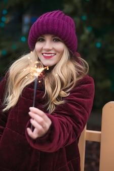 Close-up shot van een schattige blonde vrouw gekleed in warme kleren, met gloeiende sterretjes bij de kerstboom