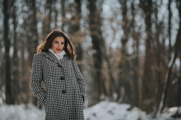 Close-up shot van een sexy blanke vrouw met rode lippenstift en een modieuze jas in een besneeuwd park