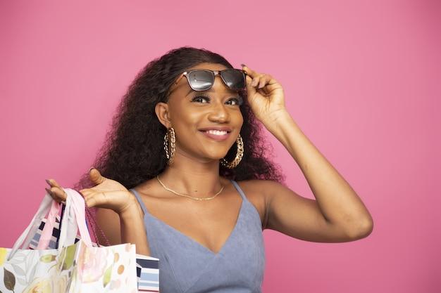 Close-up shot van een stijlvolle jonge afro-amerikaanse vrouw met boodschappentassen op een roze
