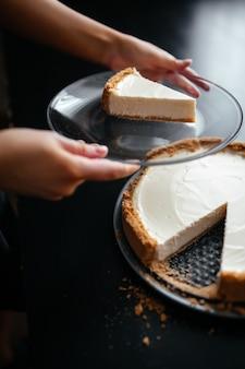Close-up shot van een stuk cheesecake op een bord naast een hele cheesecake