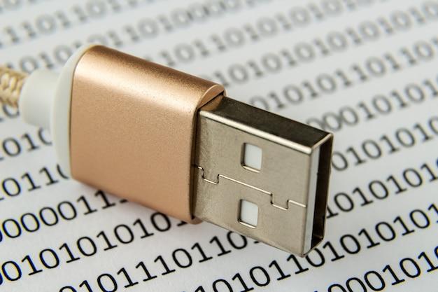 Close-up shot van een usb-kabel op een stuk papier met cijfers en codes erop geschreven
