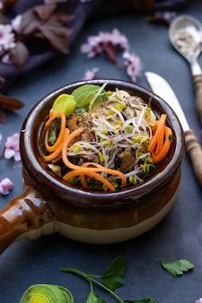 Close-up shot van een veganistische maaltijd met champignons, uien, wortelen en prei