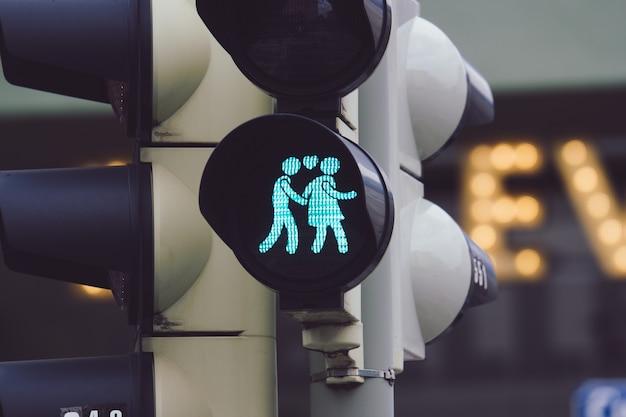 Close-up shot van een verkeerslicht met een man en een vrouw hand in hand