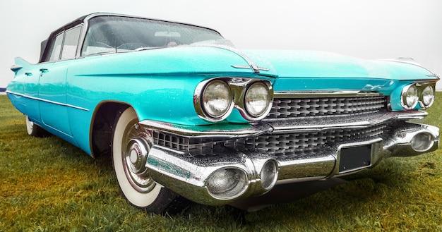 Close-up shot van een vintage turquoise auto geparkeerd op een groen veld