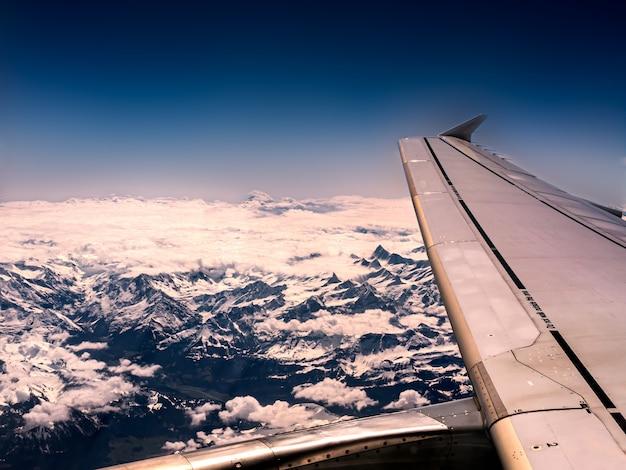 Close-up shot van een vliegtuigvleugel en bergen