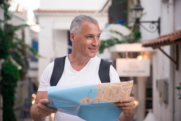 Close-up shot van een volwassen man met een kaart terwijl hij op een zomerdag buiten in de stad staat.