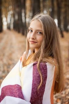 Close-up shot van een vrolijk blond meisje bedekt met warme plaid op zoek naar de camera