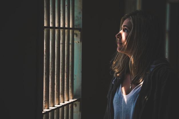 Close-up shot van een vrouw die buiten een raam kijkt van bars met de zon die op haar gezicht gloeit