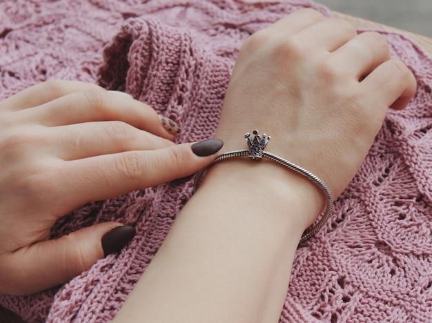 Close-up shot van een vrouw die een modieuze armband met charme hangers draagt