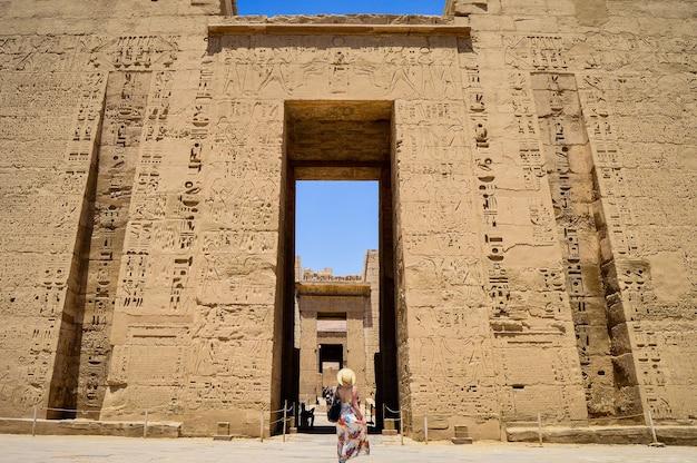 Close-up shot van een vrouw die voor een medinet habu-tempel in egypte staat