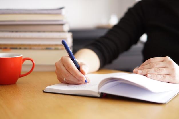 Close-up shot van een vrouw die werkt of studeert vanuit huis met een rode koffiekopje in de buurt
