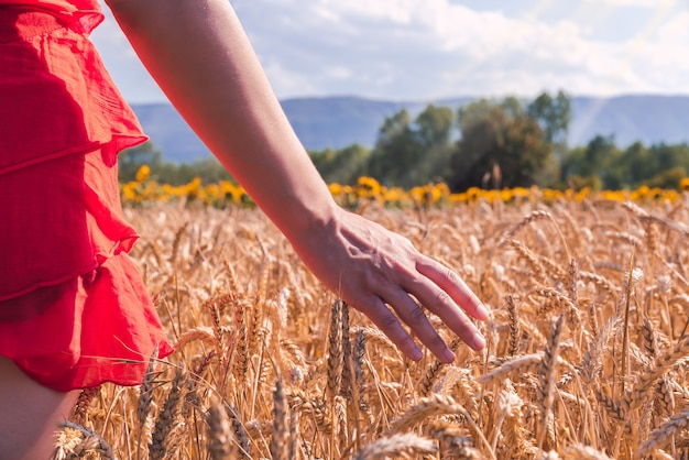 Close-up shot van een vrouw in een rode jurk in een tarweveld op een zonnige dag