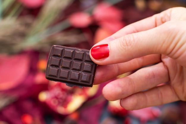 Close-up shot van een vrouw met een stuk rauwe veganistische chocolade met een onscherpe achtergrond