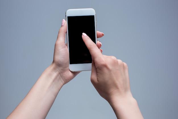 Close-up shot van een vrouw te typen op de mobiele telefoon op een grijze achtergrond. vrouwelijke handen met een moderne smartphone en wijzen met figer. leeg scherm om het op uw eigen webpagina of bericht te plaatsen.