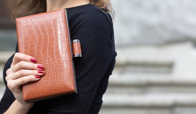 Close-up shot van een vrouwelijke hand met kleine lederen bruine clutch. ruimte voor tekst