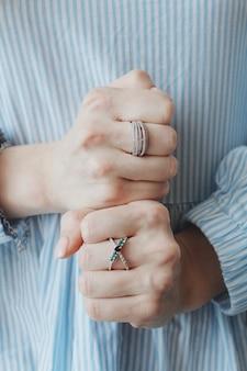 Close-up shot van een vrouwtje mooie ringen aan beide handen dragen en tonen met vuisten