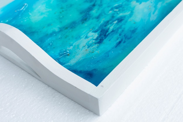 Close-up shot van een wit dienblad met epoxyhars kunst met blauwe inkt