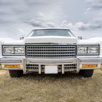Close-up shot van een witte retro auto geparkeerd op een droog veld onder een bewolkte hemel