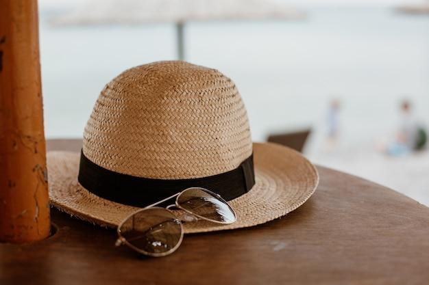Close-up shot van een zonnebril en een strooien hoed op een houten oppervlak