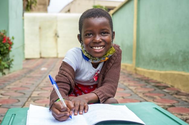 Close-up shot van een zwart mannelijk kind dat in een notitieboekje schrijft