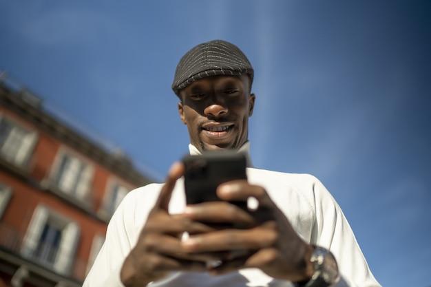Close-up shot van een zwarte man met een coltrui en een hoed die naar zijn telefoon kijkt