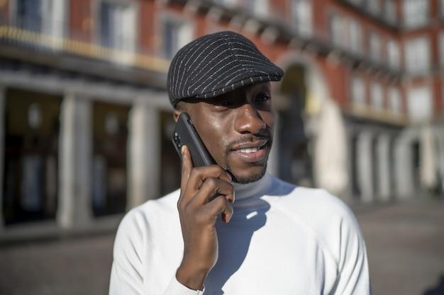 Close-up shot van een zwarte man met een hoed en een coltrui die aan de telefoon praat
