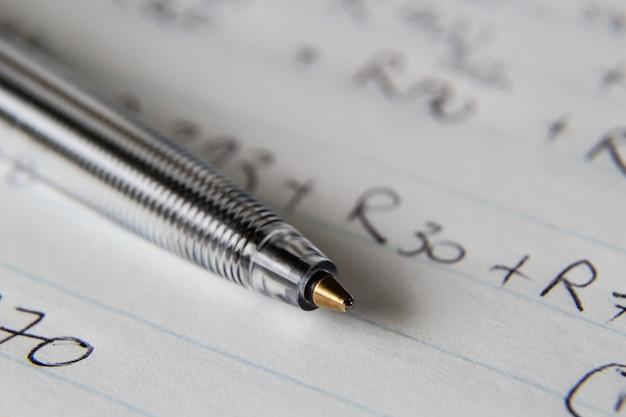 Close-up shot van een zwarte pen op een stuk papier met een aantal cijfers en codes erop geschreven