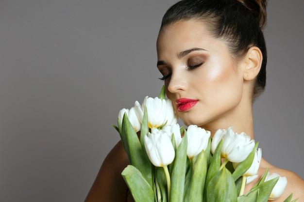 Close-up shot van elegante jonge vrouw met een boeket van een witte tulpen. studio opname over een grijze achtergrond. lege ruimte