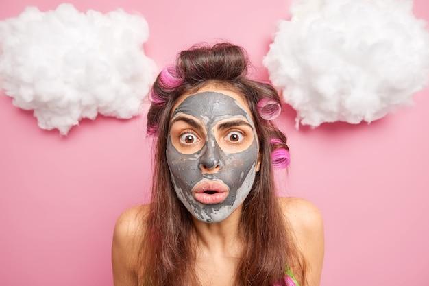 Close-up shot van emotionele donkerharige jonge vrouw met haarkrulspelden staart verbaasd reageert op iets ongelooflijks past gezichtsmasker wil er mooi uitzien en jonge poses binnen