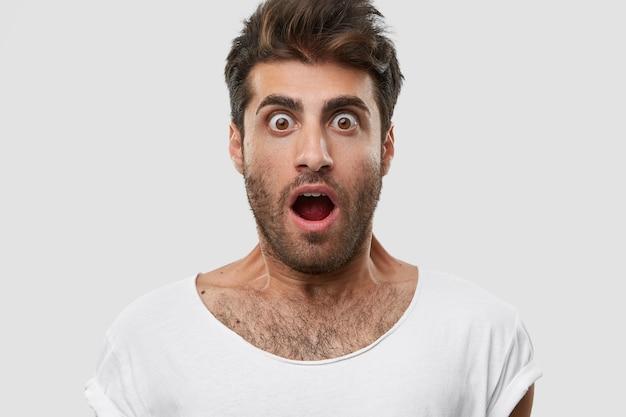 Close-up shot van emotionele verrast ongeschoren man met afgeluisterde ogen, wijd geopende mond, donkere haren, draagt casual wit t-shirt