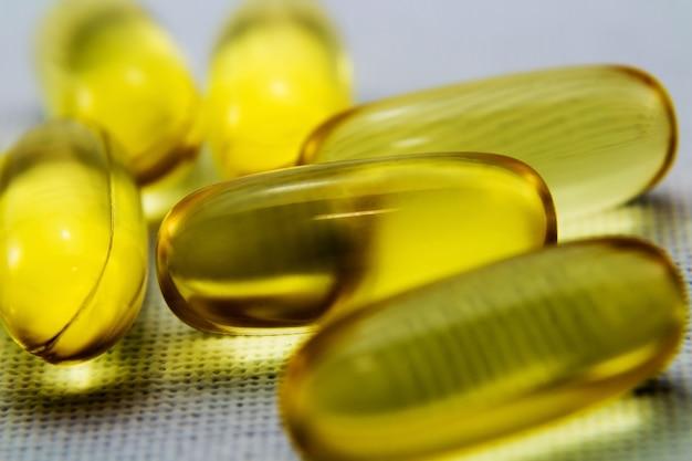 Close-up shot van enkele gele transparante capsules op een wit oppervlak