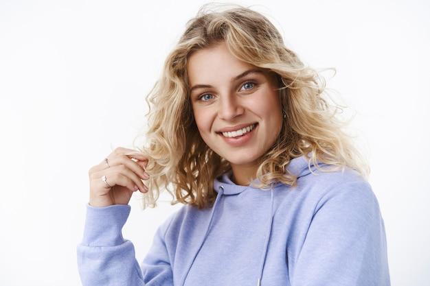 Close-up shot van flirterige en vrouwelijke volwassen schattige vrouw in de 25 met blauwe ogen die met krul spelen en naar de camera glimlachen die met interesse en verrukking kijkt als een leuk zorgeloos gesprek
