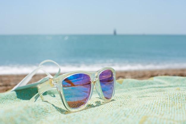 Close-up shot van funky zonnebril op het strandlaken op een zandstrand