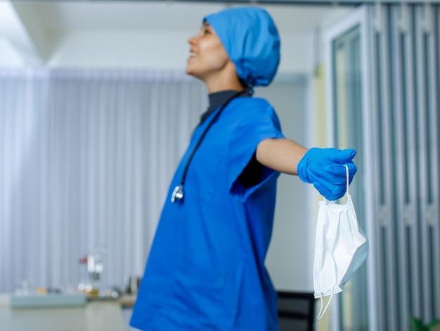 Close-up shot van gebruikt chirurgisch gezichtsmasker in de hand van vrouwelijke gelukkig lachende vrijheidsarts in blauwe ziekenhuisuniforme rubberen handschoenen en stethoscoop op onscherpe achtergrond nadat de pandemie van het coronavirus is geëindigd.