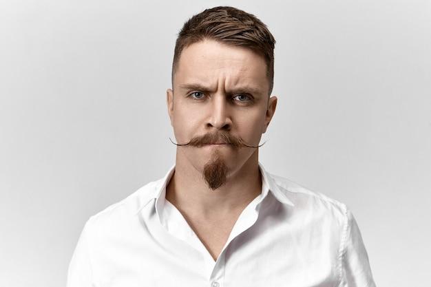 Close-up shot van gefrustreerde jonge man met stijlvol kapsel, snor en stoppels, fronsende wenkbrauwen en tuitende lippen, met een ongemakkelijke perplexe uitdrukking, bezorgd over problemen op het werk