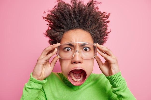 Close-up shot van gekke gekke geschokte afro-amerikaanse vrouw ziet iets angstaanjagends houdt handen op een bril houdt mond wijd open bang of geschokt draagt groene coltrui poses binnen