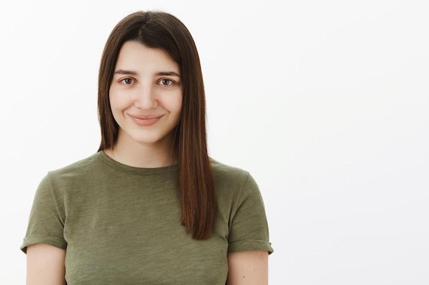 Close-up shot van gelukkig charmante en tedere schattige jonge 20s brunette in olijfgroen t-shirt glimlachend verlegen en energiek gevoel optimistisch starend betrouwbaar over witte muur