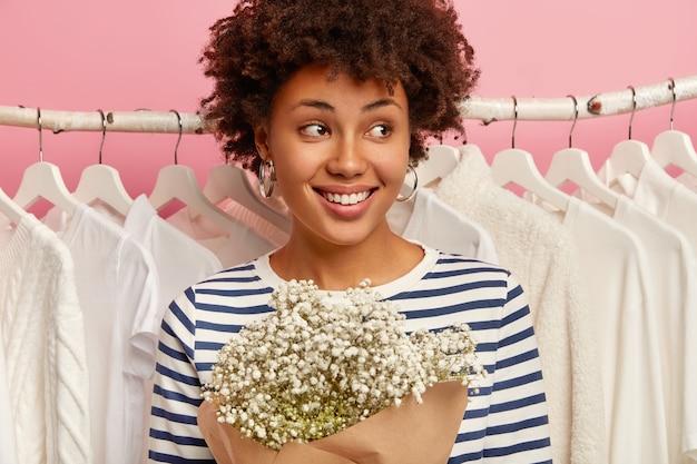 Close-up shot van gelukkig gekrulde vrouw gekleed in gestreepte outfit, staat in de buurt van kledingrekken, kijkt opzij met een glimlach. winkelen en voorjaarsschoonmaak
