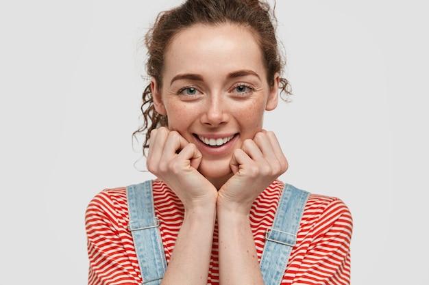 Close-up shot van gelukkig sproeterig jonge vrouw poseren tegen de witte muur