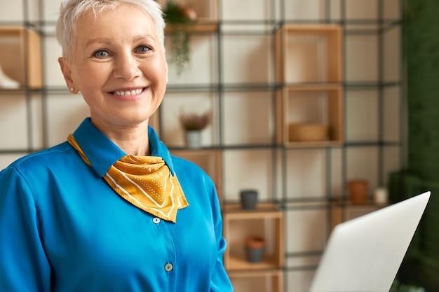Close-up shot van gelukkige vrolijke vrouw van middelbare leeftijd surfen op internet op draagbare computer. aantrekkelijke rijpe onderneemster in elegant overhemd die op afstand aan laptop werken. mensen, leeftijd en technologie