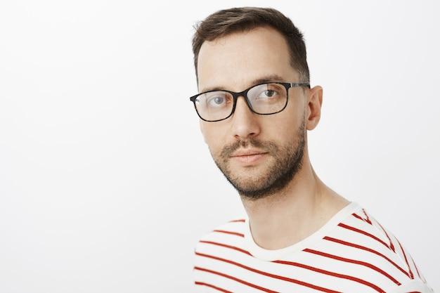 Close-up shot van gerichte slimme aantrekkelijke man in zwarte bril