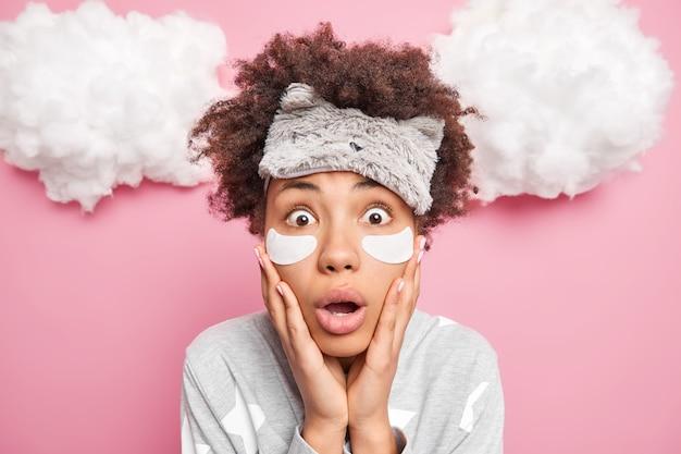 Close-up shot van geschokt gekrulde afro-amerikaanse vrouw houdt handen op wangen opent mond naar kijkt camera draagt blinddoek collageen patches onder ogen poses in pyjama bereidt zich voor op slaap