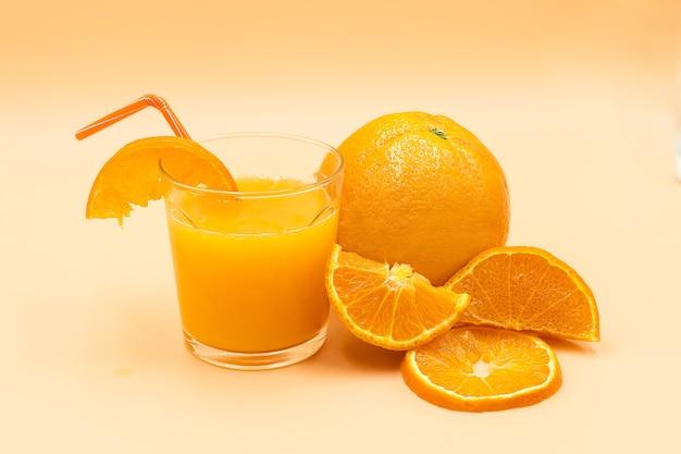 Close-up shot van gesneden sinaasappelen en een glas met jus d'orange