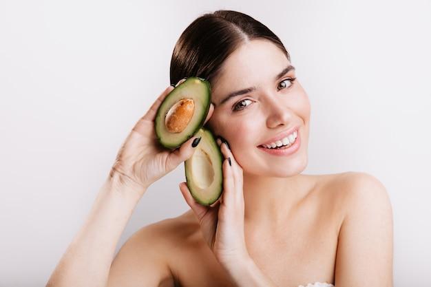 Close-up shot van glimlachende vrouw met groene ogen zonder make-up op witte muur. model toont voordelen van avocado-huid aan.
