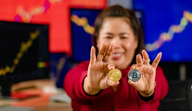 Close-up shot van gouden bitcoin elektronische token cryptocurrency geld in zakenvrouw investeerder hand in onscherpe achtergrond met computer monitor grafiek grafiek handel kopen verkopen scherm financiële markt.