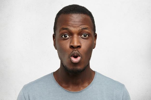 Close-up shot van grappige jonge african american man gekleed terloops lippen pruilen en wenkbrauwen verhogen