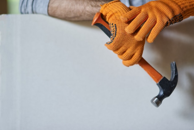 Close-up shot van handen van mannelijke bouwer die beschermende handschoenen draagt met hamer terwijl hij aan het werk is